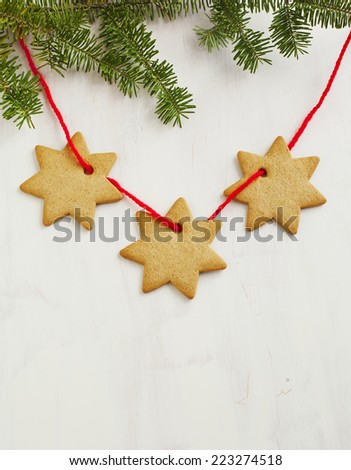 Gingerbread cookies hanging on christmas tree's branch over white wooden background. - stock photo