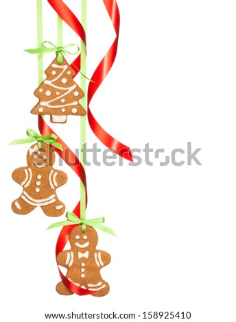 Gingerbread cookies hanging with red and green ribbon isolated on white. - stock photo
