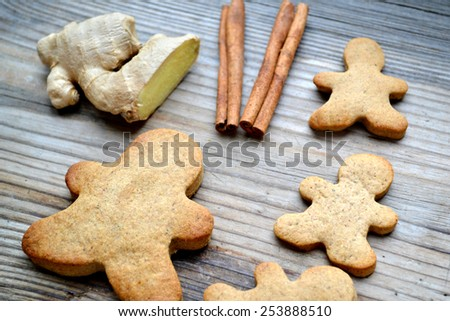 Gingerbread cookies in shape of man with cinnamon stick and ginger root on wooden table