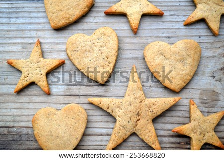 Gingerbread cookies in shapes of heart and star on wooden table
