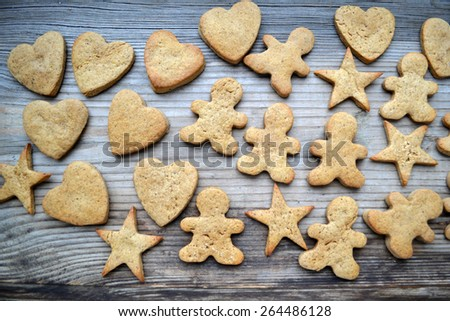 Gingerbread cookies in shapes of heart, star and man with cinnamon stick and ginger root on wooden table