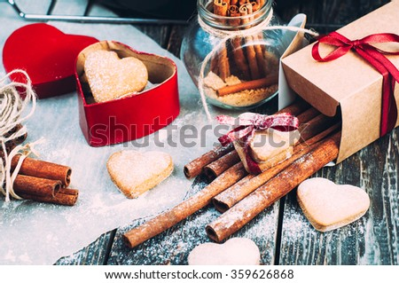 Gingerbread cookies in the shape of a heart in gift on Valentine's day.Box in the shape of a red heart on a wooden table. Gingerbread cookies and cinnamon sticks dusted with white powder. - stock photo