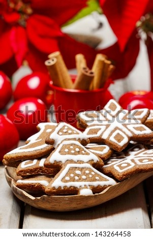 Gingerbread cookies on wooden tray, apples and poinsettia flowers in the background. - stock photo