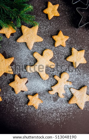 Gingerbread cookies sprinkled with powdered sugar on dark background. Festive Christmas baking. Toned.