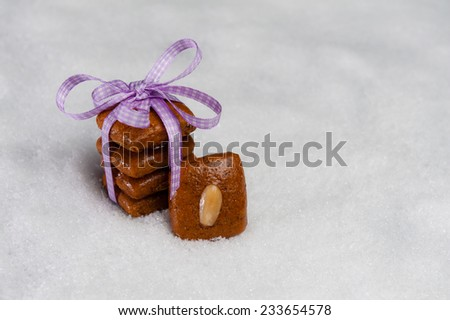 Gingerbread cookies tied with a violet ribbon on artificial snow. - stock photo