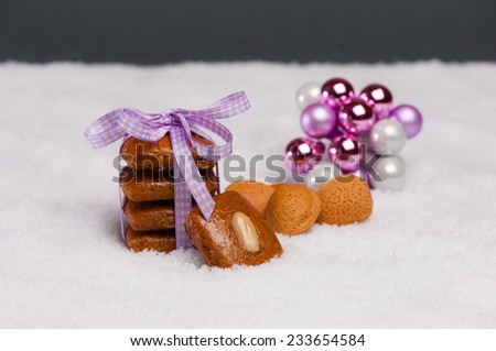 Gingerbread cookies tied with a violet ribbon on artificial snow. Almonds and some decorative spheres at the side. - stock photo