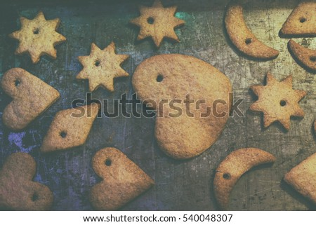 Gingerbread cookies with strings lie on baking tray. In a moment they hung on the Christmas tree/Christmas gingerbread cookies on baking tray