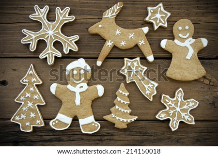 Gingerbread Cookies with White Decoration and in different Shapes on Wood - stock photo