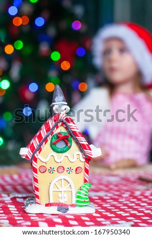 Gingerbread fairy house decorated by colorful candies on a background of little girl - stock photo