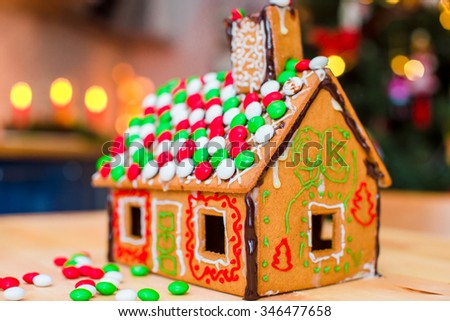 Gingerbread fairy house on a background of bright Christmas tree with garland - stock photo