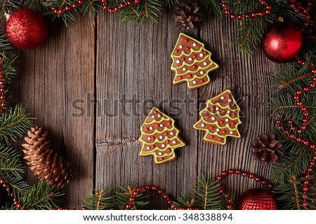 Gingerbread fur tree cookies christmas composition in new year tree decorations frame on vintage wooden table background. Top view. Traditional homemade holiday recipe - stock photo