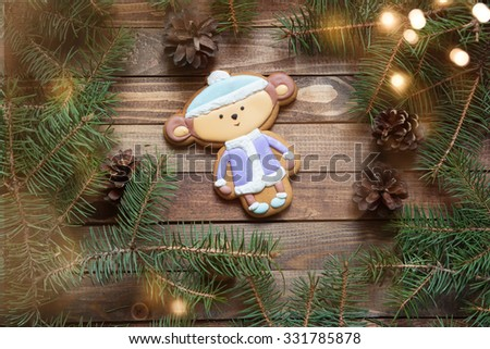 gingerbread handmade monkey on a wooden background with fir branches - stock photo