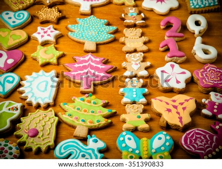 Gingerbread homemade cookies with icing colored drawings on wooden table. Toned.