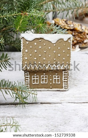 Gingerbread house by the fir branch on christmas eve table - stock photo