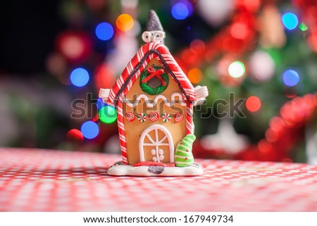 Gingerbread house decorated by sweet candies on a background of bright Christmas tree with garland - stock photo