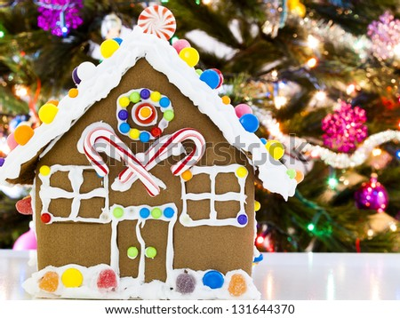 Gingerbread house decorated with candies with Christmas tree in the backgound. - stock photo