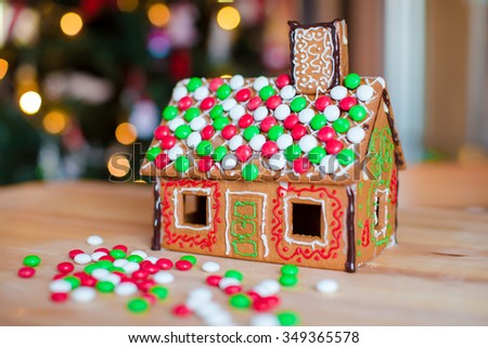 Gingerbread house decorated with colorful candies background Christmas tree lights - stock photo