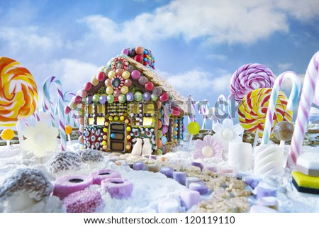 Gingerbread house in christmas landscape surrounded by candy canes and sweets