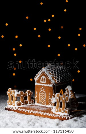 Gingerbread house in the snow under starry sky - christmas setting with copy space - stock photo