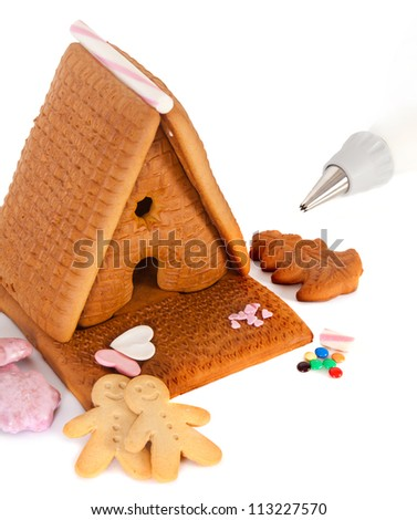 Gingerbread house with frosting and candy ready to be decorated - stock photo
