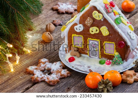 gingerbread house with tangerines and christmas lights - stock photo