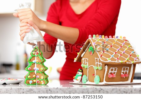 gingerbread house. Woman in holidays preparations putting glazing on gingerbread house Christmas trees.