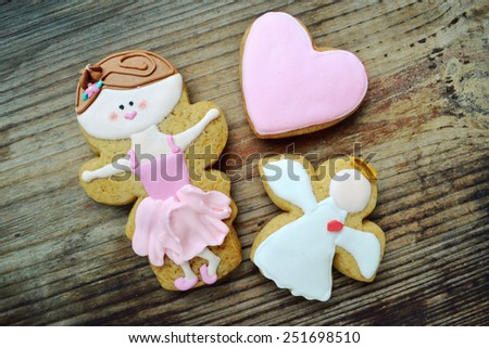 Gingerbread in a shape of heart and angel with pink and white icing and little cute ballet dancer on wooden table - stock photo