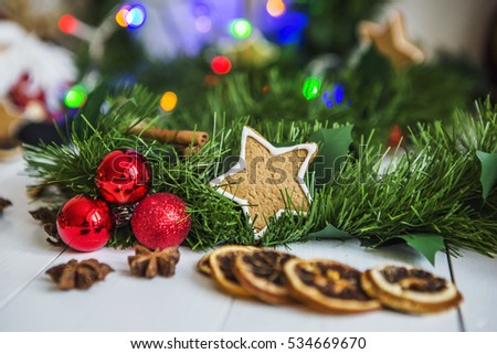 Gingerbread in the form of stars, red Christmas balls, dried lemons, cinnamon and green garland on the background of the bright lights of Christmas