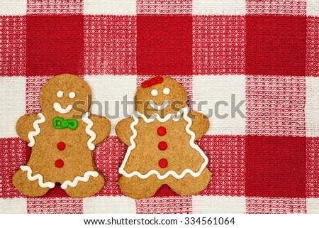 Gingerbread man and woman on a red and white checked cloth background - stock photo