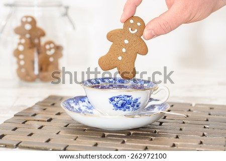 Gingerbread man being dunked into a cup of tea with jar of cookies in the background - stock photo