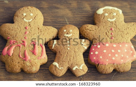 Gingerbread man cookies family on wooden table - stock photo