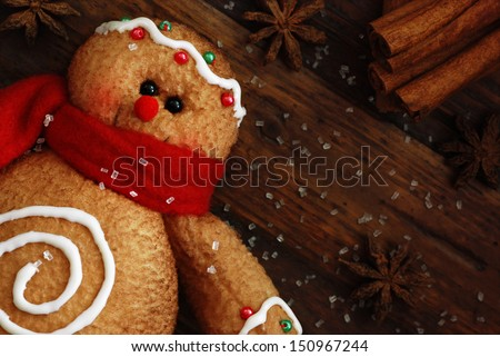 Gingerbread man (ornament made of fabric to look like a cookie) on rustic, dark wood background with sugar and spices.  Macro with shallow dof.