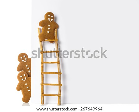Gingerbread man up a ladder of advertising board - stock photo