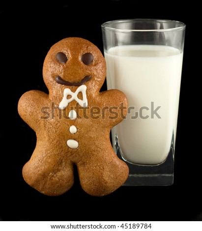Gingerbread man with a glass of milk isolated on black - stock photo
