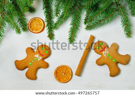 Gingerbread mans and Christmas tree branches on wooden background. Christmas food. Food photo. Christmas mood. Christmas card. Christmas symbol. Preparing to Christmas. Christmas decoration. Christmas