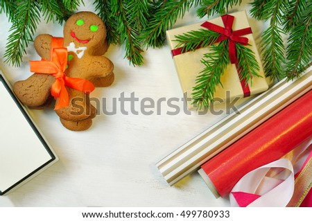 Gingerbread mans, gift box and Christmas tree branches on wooden background