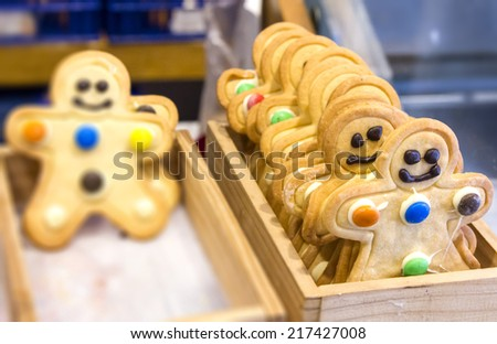 Gingerbread Men in wooden container for sale - standing out from the crowd - stock photo