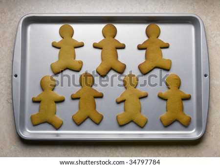 Gingerbread men on baking sheet - stock photo