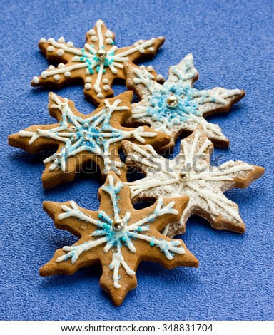Gingerbread shaped snowflakes decorated with icing and sugar sprinkling on solid blue background, selective focus - stock photo