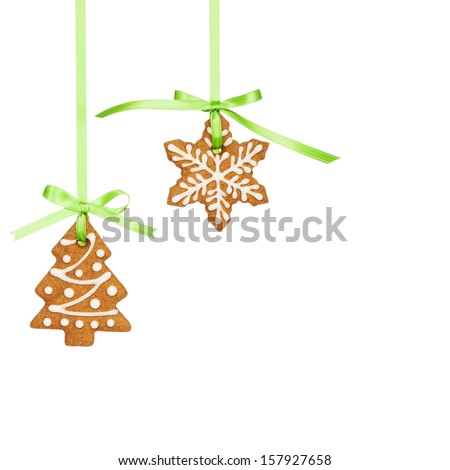 Gingerbread snowflake and Christmas tree cookies hanging by green ribbon isolated on white. - stock photo
