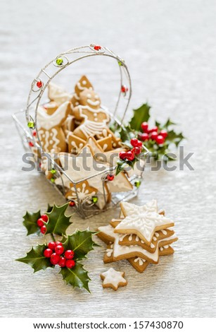 Gingerbread stars with holly branch in the decor basket on silver background - stock photo