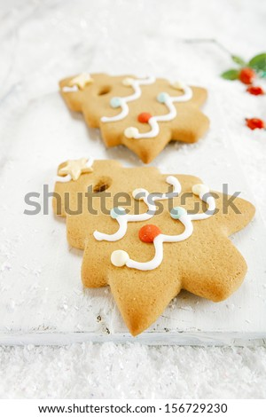 Gingerbread tree cookies on  on white wood and festive Christmas snow background, nice postcard - stock photo