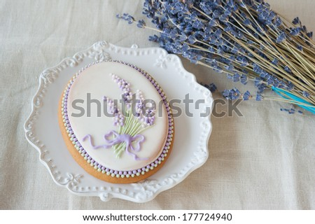 Gingerbread with a pattern of a bouquet of lavender on a white plate with a pattern near a bouquet of lavender and linen napkin