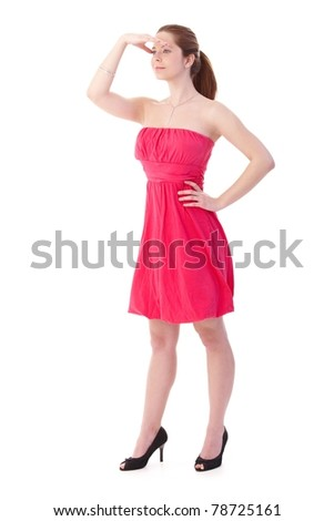 Gingerish woman looking to distance, wearing pretty pink dress and high heel shoes.? - stock photo