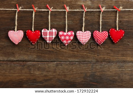 Gingham Love Valentine's hearts natural cord and red clips hanging on rustic driftwood texture background, copy space - stock photo