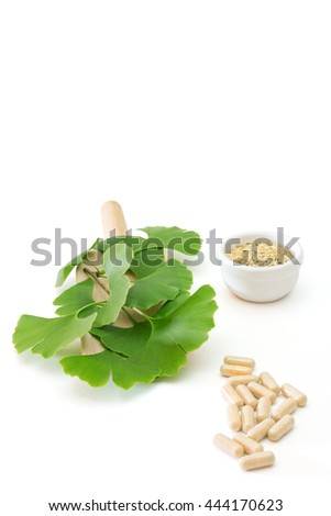 ginkgo capsules with dried herb and fresh leaves on white background