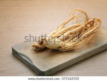 Ginseng root with wooden cutting boards - vintage filter. - stock photo
