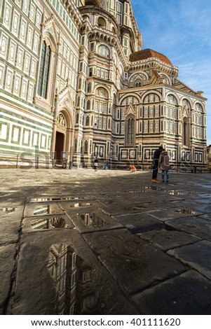 Giotto's Bell Tower reflected in a puddle in the Piazza del Duomo in Florence, Italy