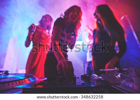 Girl adjusting deejay equipment at disco - stock photo