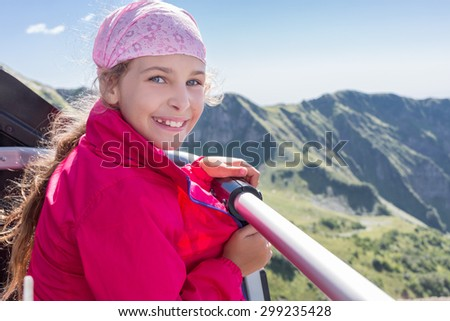 Girl admiring the mountains from the chair lift - stock photo